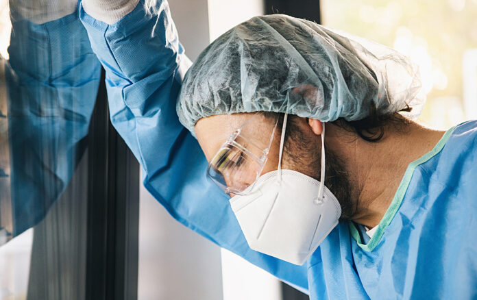 Physician in mask leaning against wall in desperation