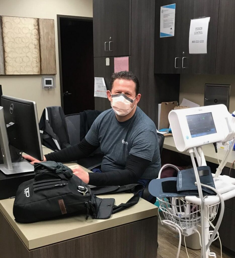 A doctor sitting at the nursing station in a medical office with a computer and vital signs station.