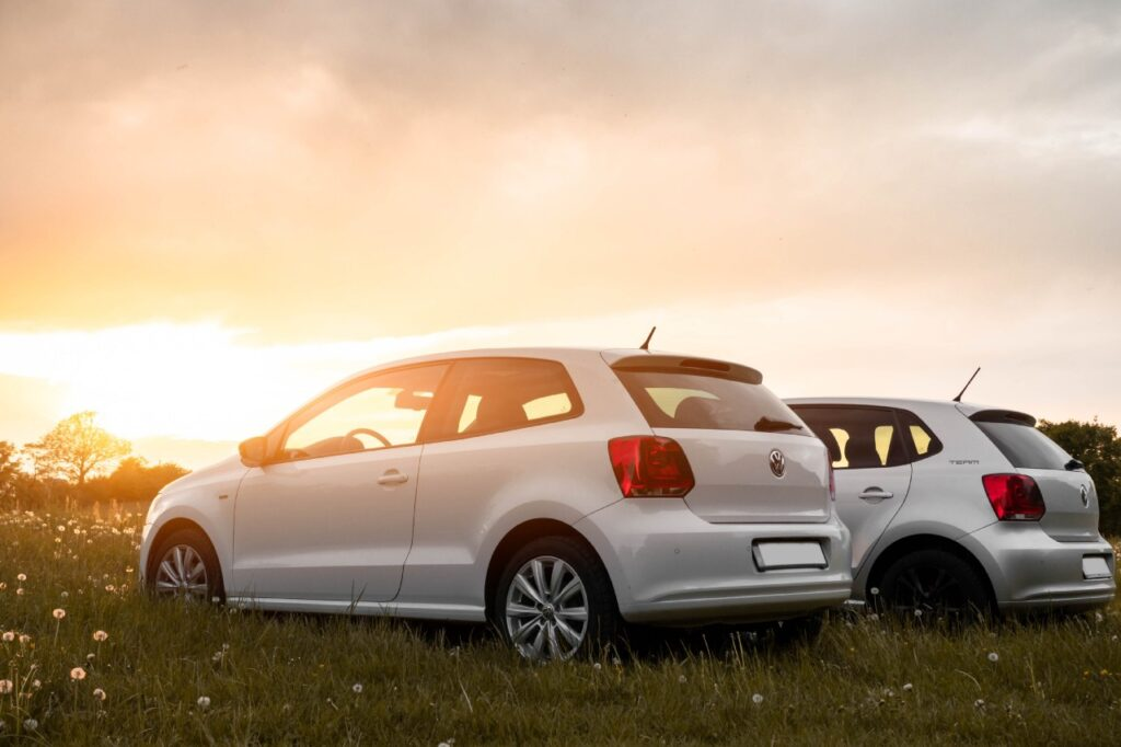 Two cars in a grassy field with the sun coming up on the horizon