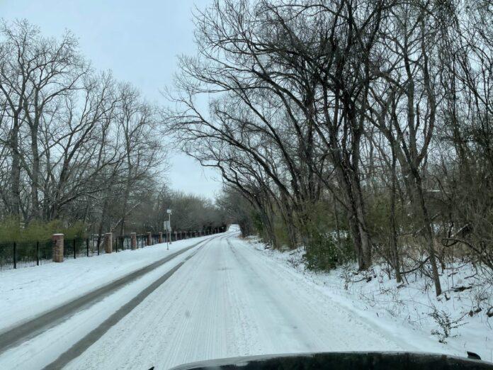 Driver's view driving down an icy road with snow covered trees
