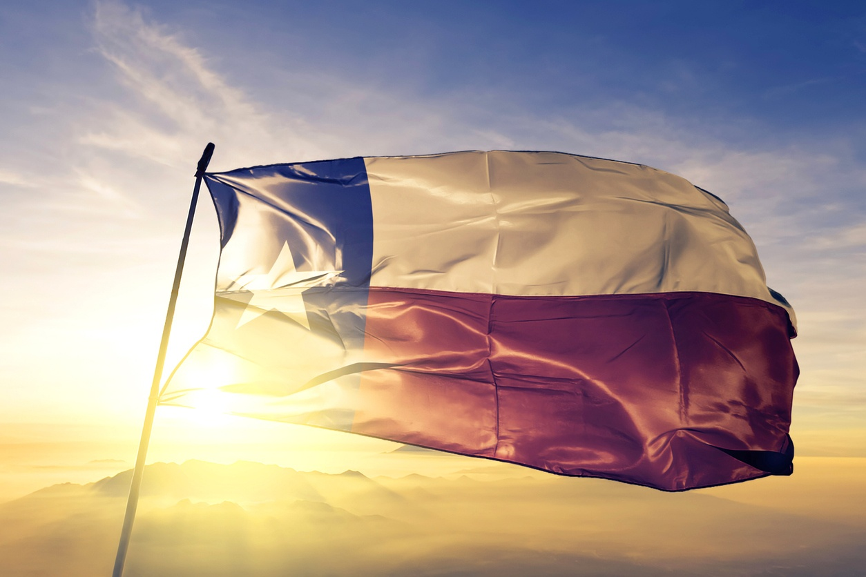 Texas flag on flagpole textile cloth fabric waving on the top with sunse